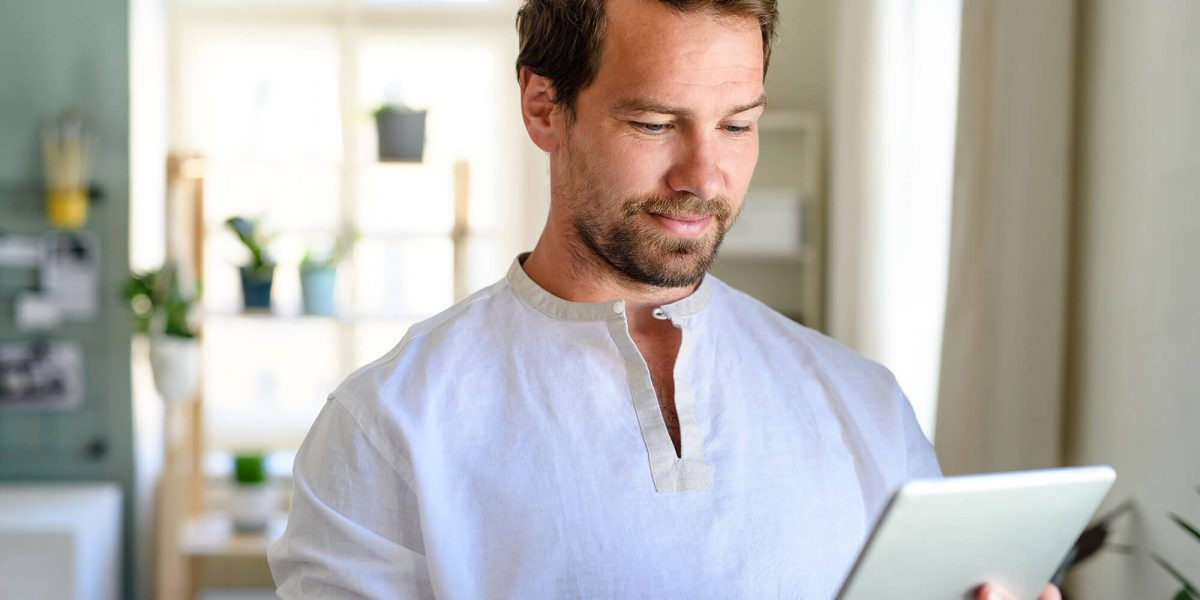 front-view-portrait-of-man-using-tablet-at-home-QH4V9GY (1)